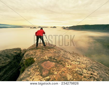 Professional Hiker And Photographer Shooting In Nature With A Digital Camera And A Tripod. Rocky Vie
