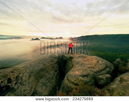 Professional Photographer And Hiker Shooting In Wild Nature With A Digital Camera And A Tripod. View