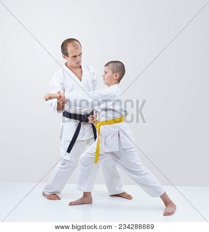 Coach With Black Belt Straightens  Karateka Boy With Yellow Belt
