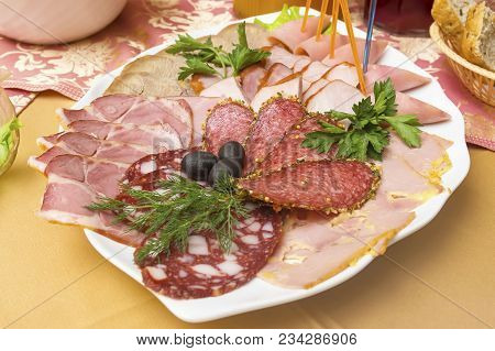 Different Meat Delicacies In A Plate On A Server Table Close-up. Cutting Of Different Types Of Sausa