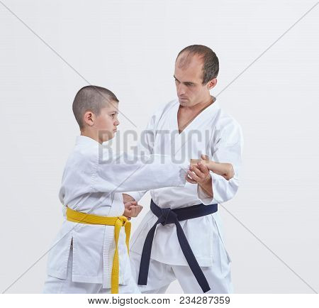 The Trainer With Black Belt Teaches Karateka Boy With Yellow Belt To Beat The Blow