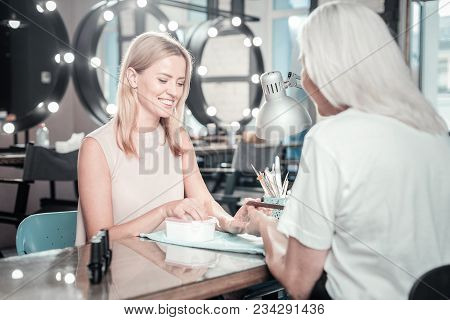 Professional Manicure. Cheerful Delighted Happy Woman Looking At Her Hands And Smiling While Having