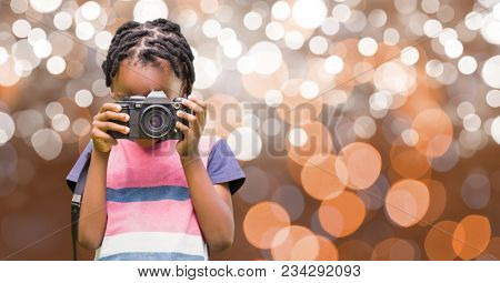 Boy photographing through camera over bokeh