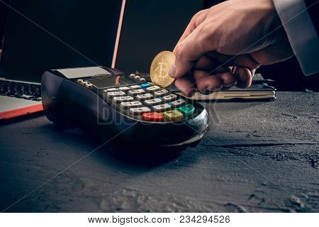 Bitcoin, Credit Card And Pos-terminal. The Golden Bitcoin In Male Hands. Cryptocurrency Bitcoin Coin