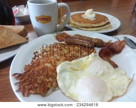 Grand Slam Breakfast with eggs, bacon, sausage, hash browns, coffee, toast and coffee, at Denny's Restaurant on April 1, 2018 in Murrieta, CA.
