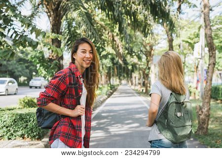 Couple Of Young Asian Women Standing Along The Street Enjoying Their City Lifestyle On Weekend Waiti