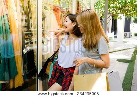 Couple Of Young Asian Women Do Shopping For A Dress In An Outdoor Mall In The Weekend Morning. Young