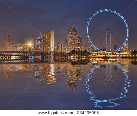 12 November 2014: Singapore - Singapore Flyer And Skyline Reflected In The Waters Of Marina Bay