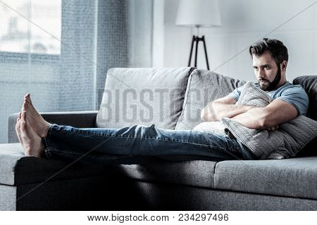 State Of Loneliness. Depressed Nice Sad Man Sitting On The Sofa And Holding A Cushion While Sufferin