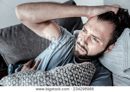 I Am Alone. Sad Cheerless Handsome Man Lying On The Sofa And Thinking About His Life While Suffering