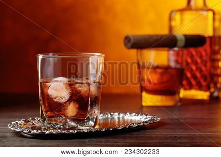Glass Of Scotch Whiskey With Natural Ice And Cigar .