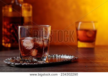 Glass Of Scotch Whiskey And Natural Ice On Old Wooden Table.