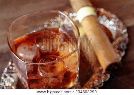 Glass Of  Whiskey And Cigar On Old Wooden Table.
