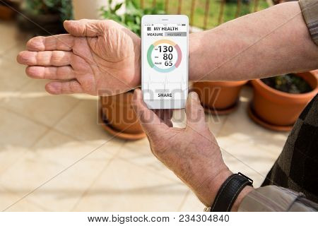An Elderly Man Measures Blood Pressure And Pulse By Mobile Phone With Medical Application