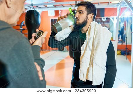 Waist Up Portrait Of Bearded Middle-eastern Man Drinking Water After Tough Training In Martial Arts