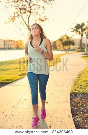 Woman jogging along a pathway in a city park in the early evening. full length photo of a Beautiful slender woman in her 30s staying healthy and fit