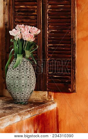A Soft Focused Bouquet Of Pink Flowers In An Old Big Vase On A Window Sill, Wooden Jalousie In The B