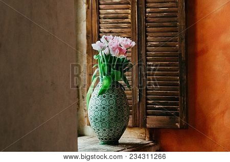 A Soft Focused Bouquet Of Pink Peony Flowers In An Old Big Vase On A Window Sill, Wooden Jalousie In