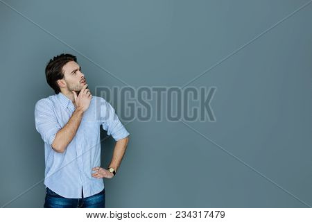 Thoughtful Look. Smart Handsome Thoughtful Man Holding His Chin And Looking Up While Standing Agains