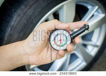 Hand Holding Pressure Gauge For Checking Tire Pressure