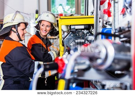 Female fire fighters loading hoses into fire engine