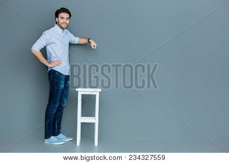 Useful Object. Nice Good Looking Handsome Man Standing Near The Stool And Holding Her Hand Above It