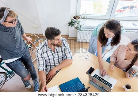 High-angle view of a four young co-workers talking and cooperating while working together as freelancers in a modern shared office space
