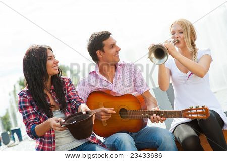 Young Friends Play The Guitar And Trumpet