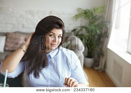 Beauty And Body Positivity Concept. Portrait Of Happy Gorgeous Plus Size Young Dark Haired Female Mo