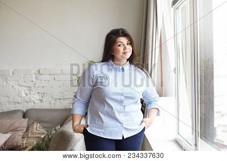 Cropped Indoor Shot Of Cheerful Body Positive Dark Haired Female Student In Stylish Xxl Clothes Smil