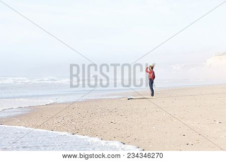 Young adult surfer with dreadlocks wearing wetsuit standing on beach near surfing spot and looking for waves covering eyes from summer evening sun by hand - surfing concept, copy space, Portugal