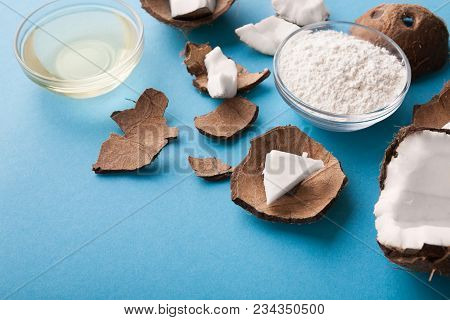 Plate With Coconut Gluten Free Flour, Water And Nuts On Blue Background, Copy Space. Organic Ingredi