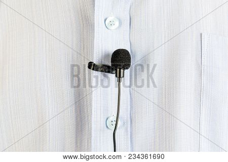 A Small Buttonhole Microphone On A Man's Shirt.