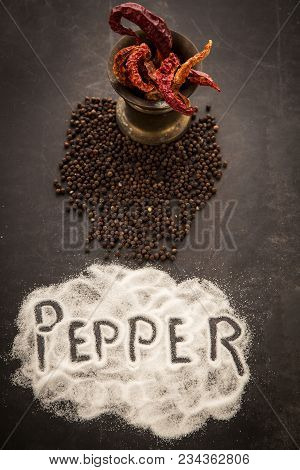 Red Hot Chili Peppers And Peppercorns On Black Metal Background, Top View. The Harm That Brings Hot