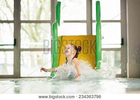 Little girl sliding down the water slide and splashing the water. Water park. Aquatic activity.