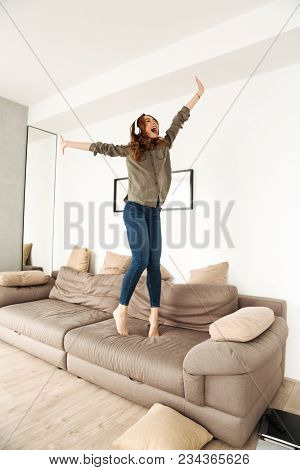 Happy joyous woman 20s in casual clothing partying in apartment and dancing on sofa while listening to music via wireless earphones