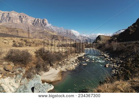 A Mountain River In A Mountainous Rocky Area Near Which There Are Power Lines On The Background Of E