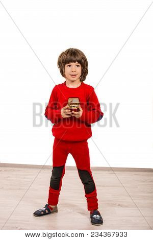 Cheerful Boy In Red Wool Clothes Holding A Musical Box