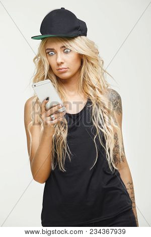 Stylish Blonde In Fashionable Clothes And Tattoos Looks Surprised At Screen Of Phone, Very Much Open