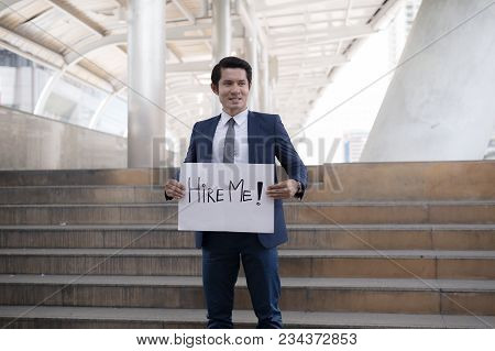 Hire Me! Handsome Businessman Wear Blue Suit Holding Poster With Hire Me Text Message While Standing