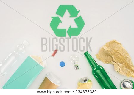 Top View Of Variation Of Types Of Trash With Recycle Sign On White