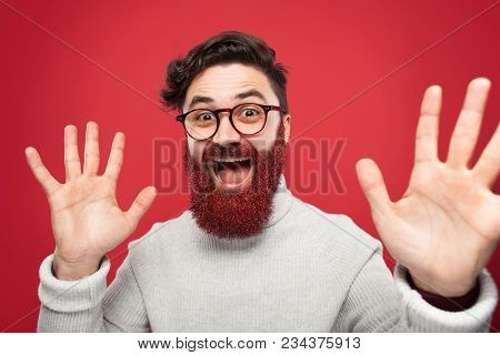 Portrait Of Young Man Posing Insanely At Camera With Beard In Red Glowing Sparkles.