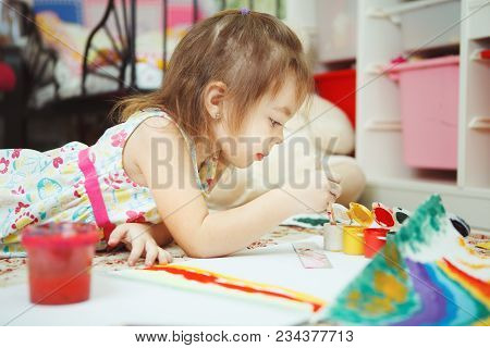 Little Creative Girl Lies On Kids Bedroom Floor Surrounded With Colorful Pencils And Bottles Of Brig