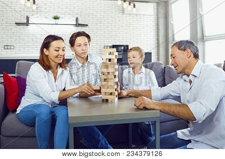 The Family Plays Board Games Gaily While Sitting At The Table Inside The Room.