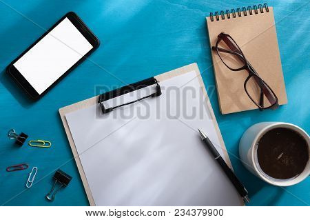 A4 Size Clipboard, Smartphone, Small Notebook, Glasses, And Coffee Cup On Blue Wood Table With Natur