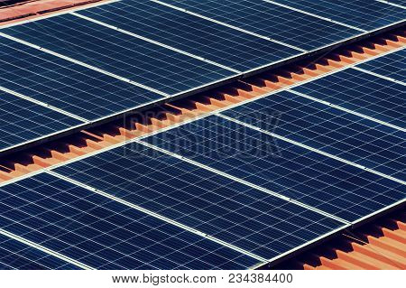 Large Photovoltaic Battery On Bower Roof, Alternative Energy. Black Solar Panel Closeup On Red Roof