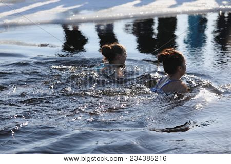 ST. PETERSBURG, RUSSIA - MARCH 4, 2018: Amateur winter swimmer at ice hole during Big Neva Cup. Winter swimmers from 12 countries aged from 12 to 78 take part in the competitions this year