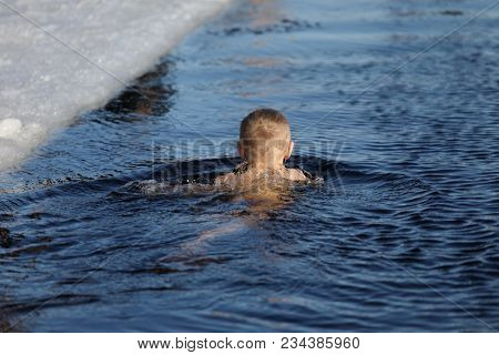 ST. PETERSBURG, RUSSIA - MARCH 4, 2018: Amateur teen winter swimmer at ice hole during Big Neva Cup. Winter swimmers from 12 countries aged from 12 to 78 take part in the competitions this year