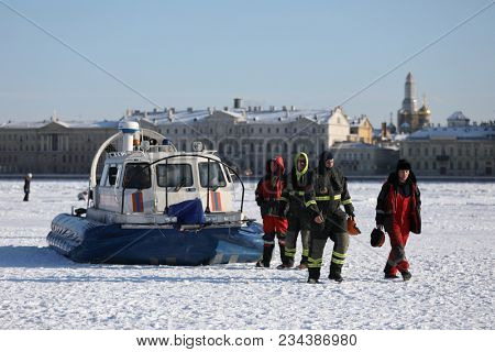 ST. PETERSBURG, RUSSIA - MARCH 4, 2018: EMERCOM staff at their hovercraft during winter swimming competitions Big Neva Cup. Winter swimmers from 12 countries take part in the competitions this year