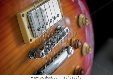 Orange Electric Guitar Close Up On Dark Background